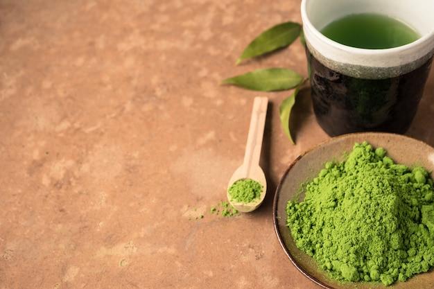 Vista superior do pó do chá verde com o copo de chá na tabela. espaço livre para o texto
