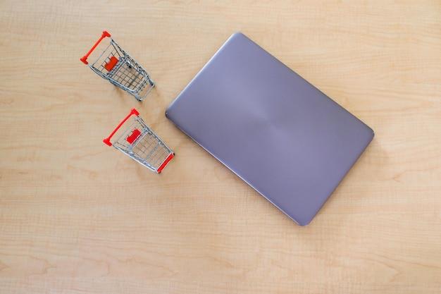 Vista superior do portátil do computador com o carro de dois supermercados na tabela de madeira.
