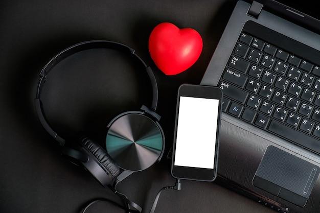 Vista superior do portátil esperto do telefone do fones de ouvido do dispositivo da cor do preto e do coração vermelho.