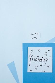 Vista superior do post-it azul de segunda-feira com carranca