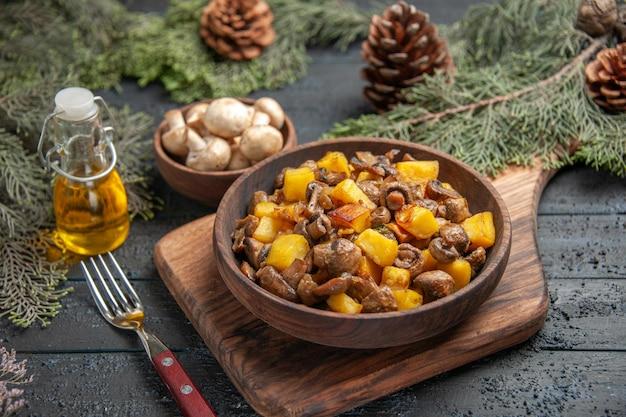 Vista superior do prato a bordo do prato de batatas e cogumelos na tábua ao lado do garfo sob a tigela de óleo de cogumelos na garrafa e galhos com cones