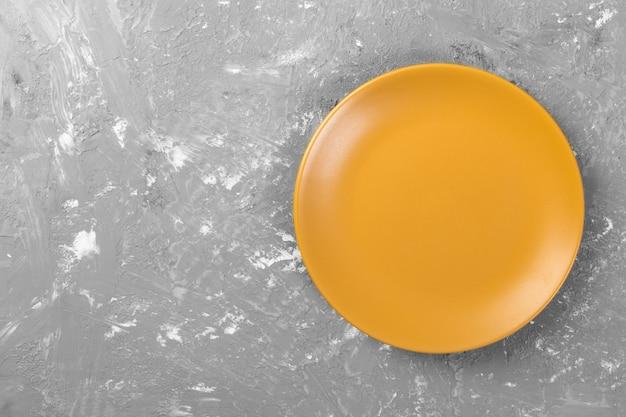 Vista superior do prato amarelo vazio redondo fosco