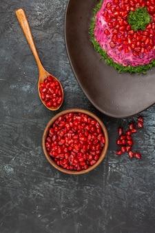 Vista superior do prato ao lado da tigela de colher de sementes de romã