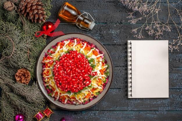 Vista superior do prato apetitoso prato de natal com sementes de romã ao lado dos galhos da árvore do caderno branco e óleo na garrafa