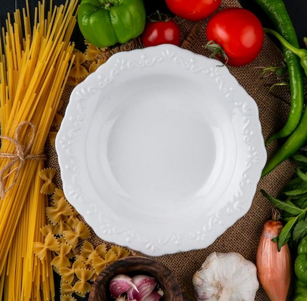 Vista superior do prato branco com macarrão cru e espaguete, tomate, alho, cebola e pimenta em um guardanapo bege