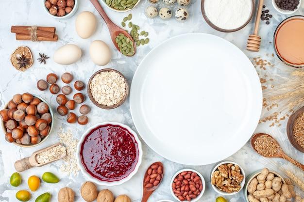 Vista superior do prato branco com ovos de geleia, nozes e sementes diferentes na massa branca, biscoito cor de açúcar, foto de noz doce