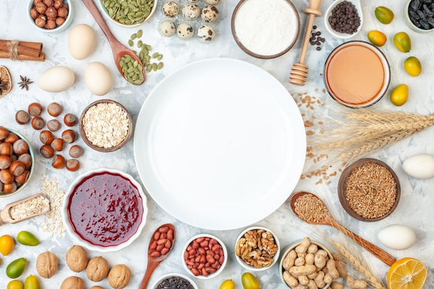 Vista superior do prato branco com ovos de geleia, nozes e sementes diferentes na massa branca, bolo de biscoito, cor de açúcar, foto de noz doce