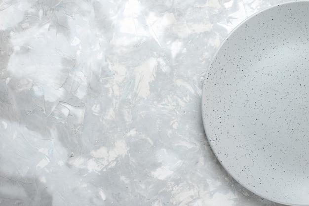 Vista superior do prato cinza vazio na luz, talheres de cozinha de prato