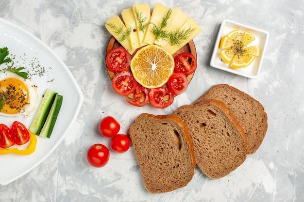 Vista superior do prato com alimentos vegetais e verduras com queijo e pão na mesa branca com vegetais comida refeição almoço café da manhã