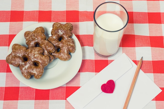 Vista superior do prato com biscoitos, copo de leite e envelope com uma carta de amor dentro de uma toalha de mesa quadriculada
