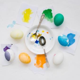 Vista superior do prato com colheres e ovos coloridos para a páscoa