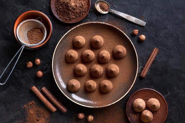 Vista superior do prato com doces de chocolate e paus de canela