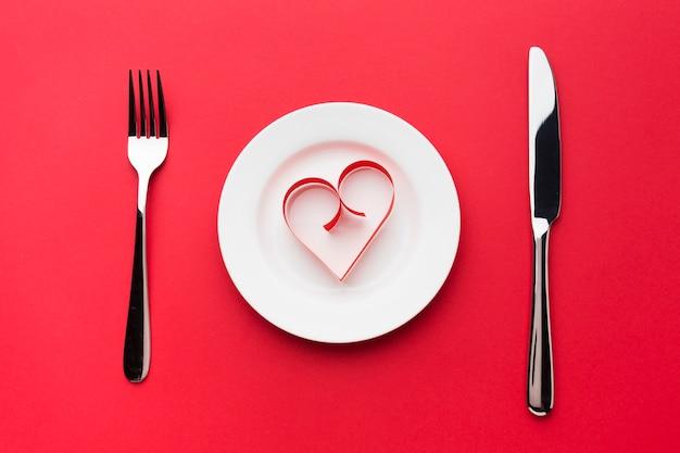 Vista superior do prato com forma de coração de papel e talheres