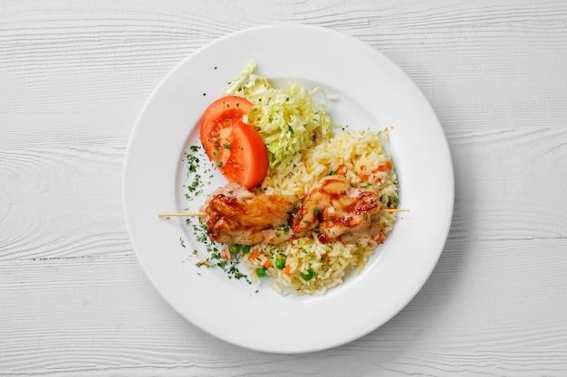 Vista superior do prato com frango shashlik, arroz com ervilhas e salada de repolho