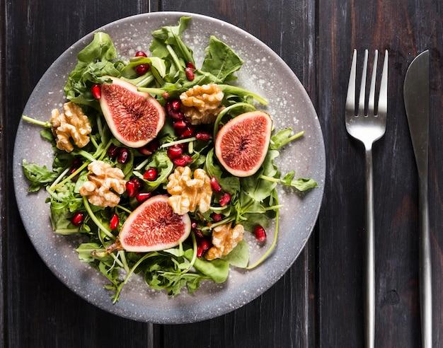 Vista superior do prato com salada de figo outono e talheres