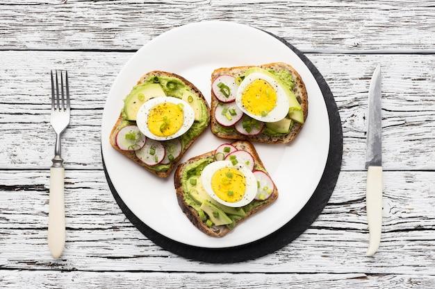 Vista superior do prato com sanduíches de ovo e abacate e talheres