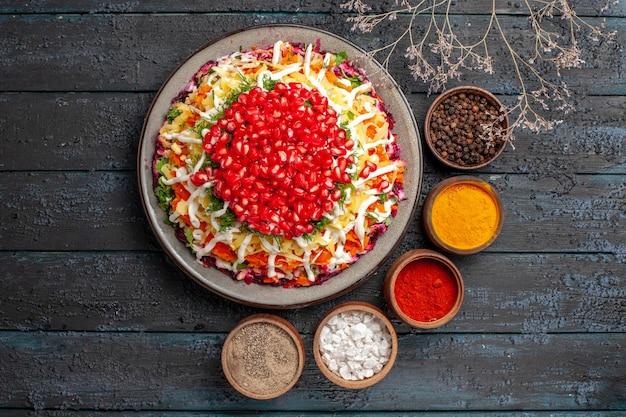 Vista superior do prato com sementes de romã cinco tigelas de especiarias ao lado do prato de natal com sementes de romã e galhos de árvores