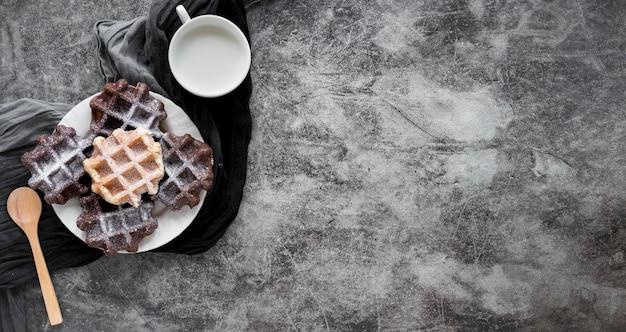 Vista superior do prato com waffles cobertos de açúcar de confeiteiro