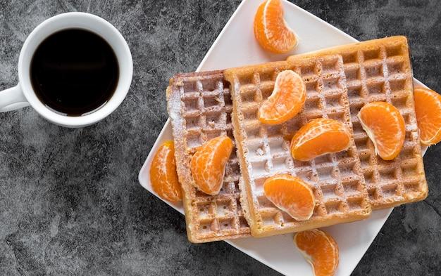 Vista superior do prato com waffles e tangerinas