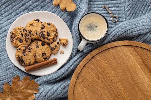 Vista superior do prato de biscoitos com uma xícara de café e folhas de outono