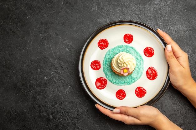 Vista superior do prato de bolinho apetitoso bolinho no prato branco nas mãos sobre o fundo escuro