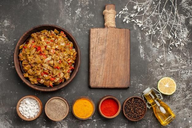 Vista superior do prato de comida apetitosa de feijão verde e tomate ao lado da tábua de madeira, especiarias coloridas, limão e garrafa de óleo na mesa