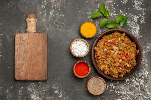 Vista superior do prato de especiarias com feijão verde ao lado das tigelas com folhas de especiarias coloridas ao lado da tábua de madeira e galhos de árvores na mesa escura