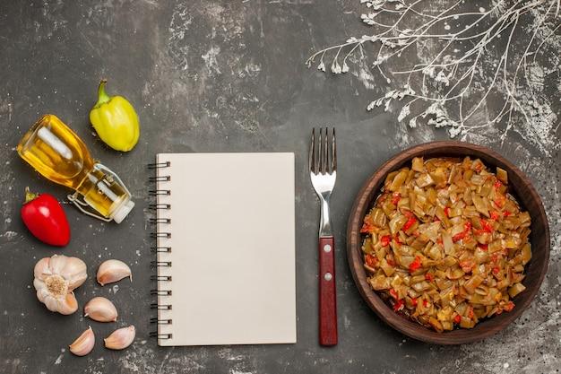 Vista superior do prato de feijão com alho e óleo de pimentão na garrafa ao lado do garfo, caderno branco e prato de feijão verde e tomate na mesa