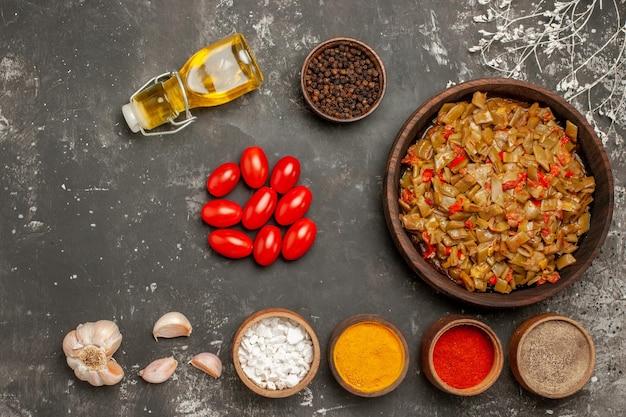 Vista superior do prato de feijão verde de feijão verde com tomate ao lado da garrafa de tomate alho da tigela de óleo de especiarias na mesa escura