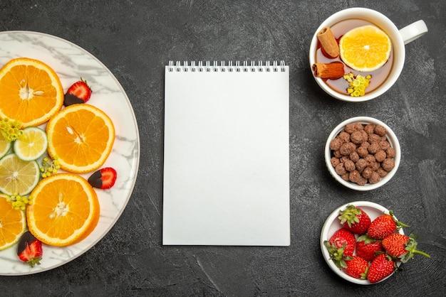 Vista superior do prato de frutas com fatias de laranja e limão morangos cobertos com chocolate ao lado do caderno uma xícara de chá de nozes e morangos