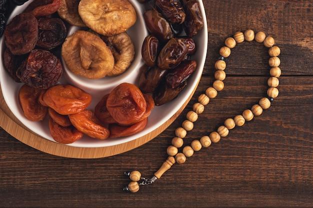 Vista superior do prato de frutas secas, rosário de madeira em fundo de madeira marrom, conceito iftar, ramadã, feriado muçulmano