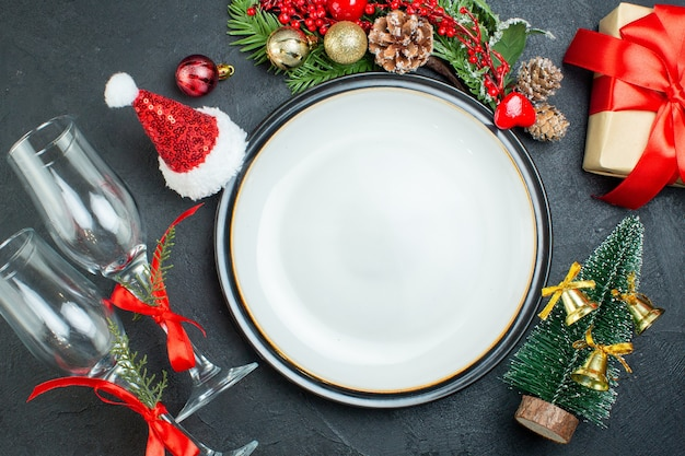 Vista superior do prato de jantar árvore de natal ramos de abeto coníferas cone caixa de presente chapéu de papai noel cálices de vidro caídos em fundo preto
