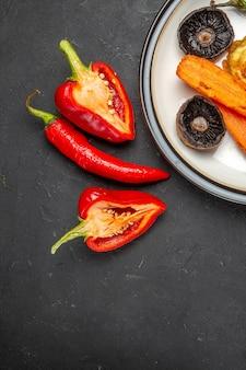 Vista superior do prato de legumes com legumes assados, toalha de mesa vermelha, pimentão, pimenta