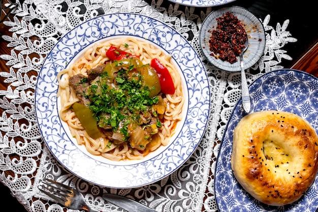Vista superior do prato de macarrão, guarnecido com ervas e pimentões refogados de cordeiro