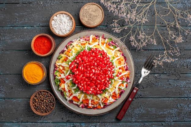 Vista superior do prato de natal cinco tigelas de especiarias coloridas e garfo ao lado dos galhos da árvore e o prato do prato de natal
