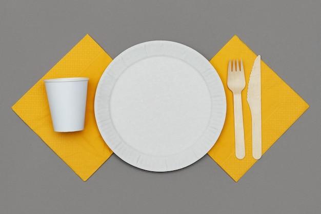 Vista superior do prato de papel branco, copo de papel, garfo de madeira e faca em guardanapo laranja em fundo cinza. conjunto de talheres descartáveis ecológicos de material natural.
