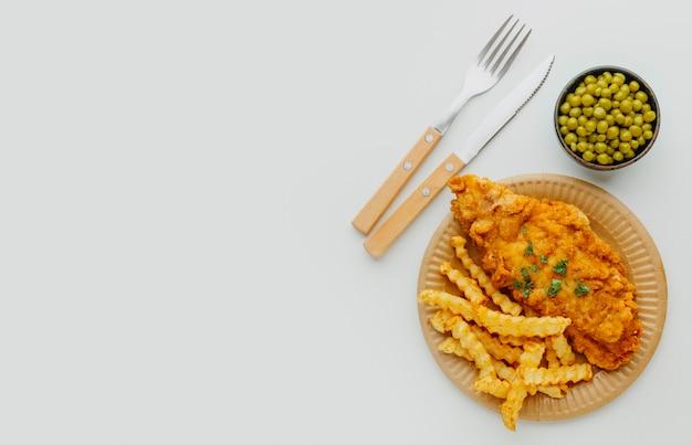 Vista superior do prato de peixe e batatas fritas com ervilhas e copie o espaço