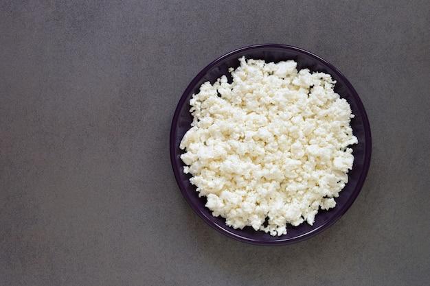 Vista superior do prato de queijo cottage na mesa escura