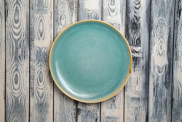 Vista superior do prato de vidro vazio verde ed na superfície cinza-rústica