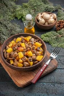 Vista superior do prato e galhos tigela de madeira com batatas e cogumelos na tábua ao lado do garfo sob a garrafa de óleo tigela de cogumelos brancos e ramos de abeto com cones