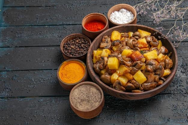 Vista superior do prato e prato de temperos com batatas, cogumelos e temperos coloridos ao redor