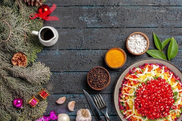Vista superior do prato e ramos de abeto apetitoso prato de natal com alho e limão tigela de óleo e especiarias ao lado da faca do garfo e ramos de abeto com cones