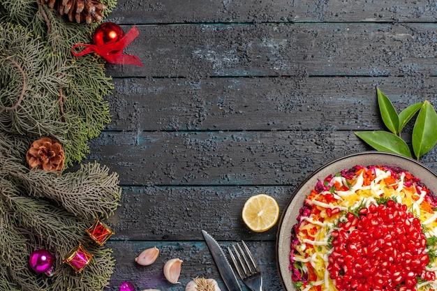 Vista superior do prato e ramos de abeto apetitoso prato de natal com faca de garfo de alho-limão e ramos de abeto com cones