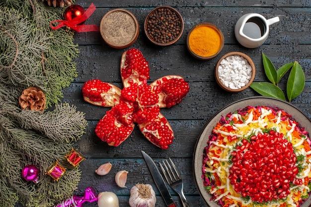 Vista superior do prato e ramos de abeto apetitoso prato de natal com uma tigela de romã com limão e óleo e especiarias ao lado da faca de garfo e ramos de abeto com cones