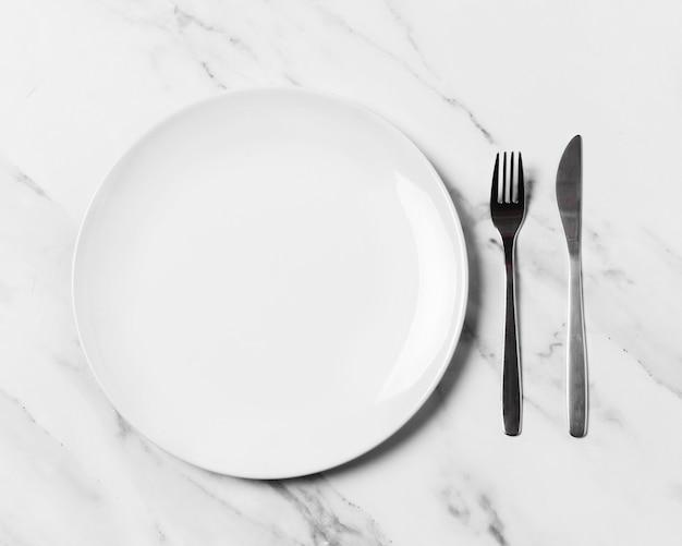 Vista superior do prato e talheres na mesa de mármore
