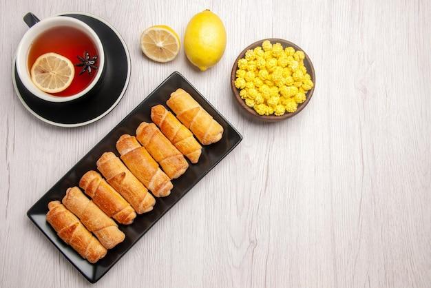 Vista superior do prato escuro de sobremesa, tigela de limão com doces e uma xícara de chá com limão ao lado do prato escuro de massa tubular na mesa branca