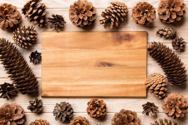 Vista superior do prato festivo com pinhas na madeira, conceito de jantar de ano novo