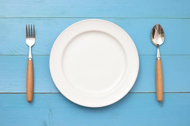 Vista superior do prato, garfo e colher em fundo de madeira