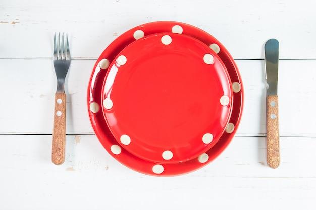 Vista superior do prato, garfo e faca no fundo de madeira