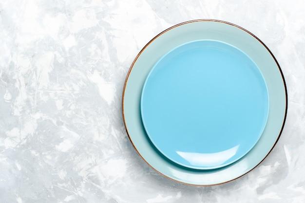 Vista superior do prato redondo vazio azul ed na mesa branca